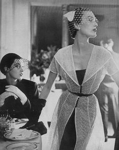 April Vogue 1950  Barbara Mullen and Mary Jane Russell  Wearing a black crepe rayon sheath dress with a low cut dress of white eyelet organdie. Photographed by Lillian Bassman.