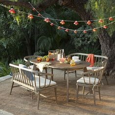 Table under strands of lights. Outdoor furniture by West Elm. via Emily Henderson.