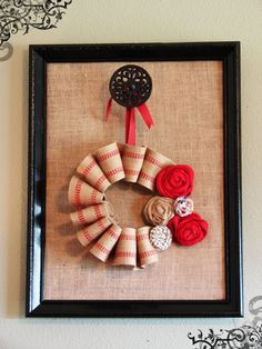 Great wall hanging made with a repainted frame, burlap backing, gathered burlap ribbon, and various rosettes.