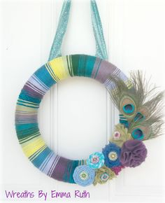 Peacock Feather Yarn Wreath with lots of color and flower embellishments. via Etsy.