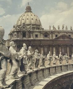Statues of popes and saints on the colonnade of St. Peter's Square, and Michelangelo's dome on St. Peter's Basilica.
