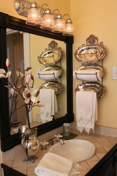 Wine bottle rack for towels, classed up with some oval silver trays.