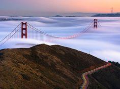 Tra le nuvole Fotografia di Michael Perry  Mentre il sole tramonta sul San Francisco Golden Gate Bridge, la nebbia si mescola con nuvole basse per sommergere quasi completamente la struttura