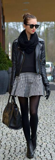 Medias tupidas, botines planos, falda corta vuelo, jersey cuello vuelto, cazadora cuero, bufanda, recogido. Blanco y negro.