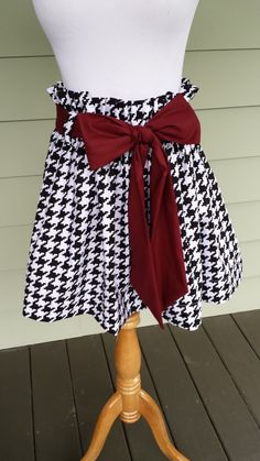 "@Maryam Butler Women's boutique gameday skirt ""The Derby Skirt"" in black & white large houndstooth with a garnet sash,"