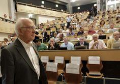 """Entre los asistentes estaba el físico británico Peter Higgs, quien da nombre al bosón, uno de los científicos que predijo su existencia en los años 60. Su entrada en el auditorio ha sido recibida con un estruendoso aplauso, cinco minutos antes del comienzo de la conferencia, que arrancaba con un """"esta es la presentación de los últimos resultados de la búsqueda de una cierta partícula.., he olvidado el nombre"""", a manos del director del CERN, Rolf Heur. El nuevo bosón tiene una masa de 125,3 más/m"""