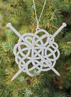 Celtic wood ornament depicting yarn & knitting needles
