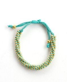 Unique and attention-getting, these twists of colored thread and golden beads cinch around your wrist to brighten any day.