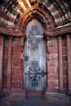 It's a side door to the exquisite red limestone Cathedral of St Magnus, Kirkwall, Orkney. The setting sun filters through the alleys between the buildings opposite the cathedral plaza, giving dramatic illumination to the cathedral facade  Note: the design in the metalwork