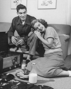 teenage couple listening to records and enjoying milk and cookies,1948