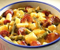 In a 3-quart casserole, stir together the bratwurst or Polish sausage, potatoes, green beans, soup, cheddar cheese, and onion.