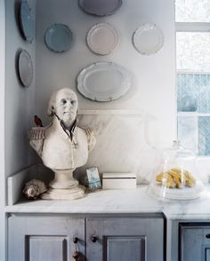A bust and an arrangement of hanging plates in Kay O'Toole's white kitchen