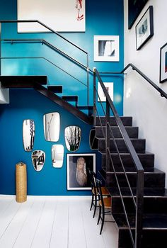 Tour a Stylish Parisian Duplex with a Modern Vision// Blue entryway with accent wall, modern staircase, and collage of mirrors