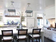 Elegant beach kitchen.  Large lantern pendants + caned counter stools