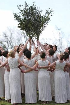 On March 25, 2004, the torch lighting ceremony for the Athens 2004 Olympic Torch Relay took place at the Ancient Olympia sanctuary. Actresses portraying priestesses dance around other priestesses who are holding olive branches, symbolizing peace and freedom, high above them in this photo.  (Photo credit: Xinhua)