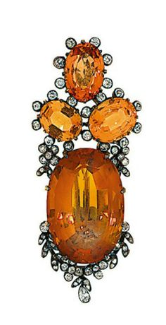 A late 19th century citrine, topaz and diamond brooch  The large oval-cut citrine to an oval-cut orange topaz three-stone surmount framed by old-cut diamond floral accents, circa 1890. (one diamond deficient)