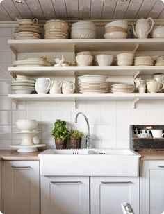 a fireclay apron sink, open shelves and a v-groove ceiling give a kitchen a more farmhouse/country feel.