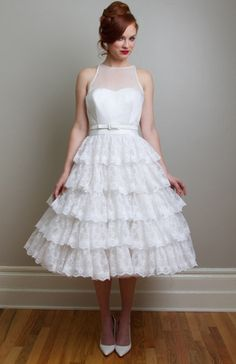 Lucy Short Wedding Dress - Flutter in layers of dainty floral lace. Lucy creates the playful inspiration of vintage tea length wedding dress. Paired with a classic sleeveless bodice of satin and sheer organza in silk or poly. Bridemaids?