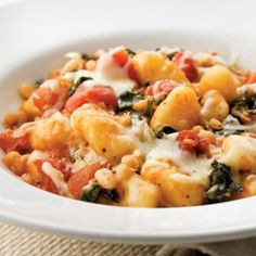 In this one-skillet supper, we toss dark leafy greens, diced tomatoes and white beans with gnocchi and top it all with gooey mozzarella. Serve with a mixed green salad with vinaigrette. - gnocchi, nhoqui, massa, pasta, jantar, almoço -