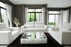 Crisp clean living room with striped white furniture, glass-top coffee table, dark brown rug