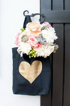 d.i.y. black canvas tote with hand painted gold heart filled with hand-picked flower market succulents, ranunculus, & roses.