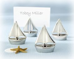 "When the sea beckons, love sets sail near the splendor of a sun-drenched shore. Create the ambiance only a beach wedding can inspire by making your tables an ocean full of glistening silver sailboats with these ""Shining Sails"" Place Card Holders-each one a paragon of stunning simplicity. The sailboats measure 1 1/2"" x 1 ¼"" x 1/2"".    Sold as a set of four.  #weddingfavors #sail #boat #placecards"