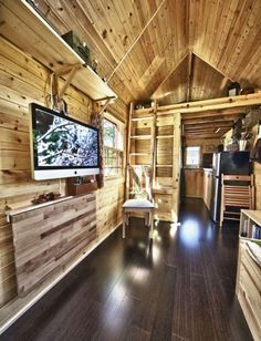 tiny house on wheels with a tiny kitchen,  a hanging TV, and a fold out table