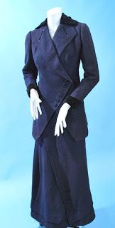 Slubby navy wool 1910-1915 walking suit. Imaginative closure design on the jacket with velvet cuffs and collar, lined in silk satin, with old label. Back closing skirt with top stitched asymmetrical pleat across skirt and along the hem.