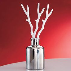 """WINTER WHITE DIFFUSER HOLDER A trio of porcelain branches rests in a silvery metallic bottle for a crisp, modern feel. Use with our fragrance oils, sold separately. Bottle: 4 1/4"""" h, 2 3/4"""" dia."""