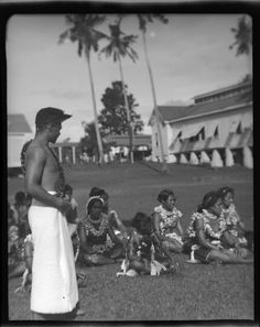 Group of women dressed alike sitting on grass, and man in white skirt standing. Creator/Contributor: Lambert, Sylvester Maxwell, 1882-1947, Photographer Date:between 1919 and 1939 Contributing Institution: UC San Diego, Mandeville Special Collections Library