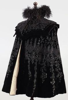 Cape 1890, black silk velvet embroidered with jet beads tonal a large floral decoration, cape collar trimmed with black ostrich scalloped cutout.