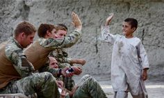 Royal Marines from D Company, 40 Commando with an Afghan child in Sangin, Helmand Province. Photograph By Sarah Yuen / © Crown copyright