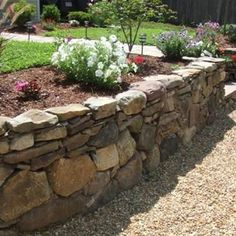 Ranch-style homes often feature a veneer of stone on the bottom third of the home, so a fieldstone wall like this one makes a great balance in the landscape. Design by Lewis Garden & Landscape in Whitinsville, MA. Learn more about materials options for a Ranch-style home here: http://www.landscapingnetwork.com/walls/materials.html