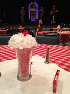 50's sundae centerpieces we made for a 50's rock'n'roll themed holiday party. Coca-Cola glass, shredded pink paper, mum, red pom pom, red and white striped straw. Easy, inexpensive and cute!