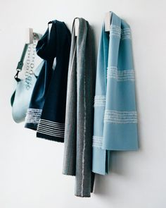 In hues of blue, gray, and cream, these scarves evoke the look of men's suiting. The stripes are created with pieces of yarn needlefelted along the length or width of the scarves. The navy scarf shows how needle-felting looks on both sides: The design on one side is sharp