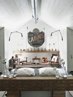 In the master bedroom, a vintage French sewing cabinet doubles as a headboard. The motor-court sign was discovered at a local antique show and serves as an eye-catching and whimsical focal point around which additional seating and light fixtures are placed.