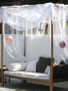 Outdoor Daybed made from old bed frame and enhanced with sheer curtains and paper lanterns.