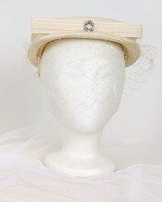 1950's ivory straw hat with veil (front view) | Wide flat top with ribbon trim and straw bow in front decorated with rhinestone brooch. Delicate veil in front and fabric prongs on the inside to keep it on the head