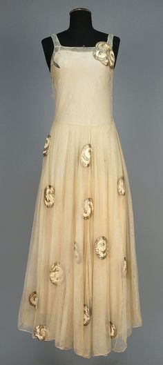 "LANVIN COUTURE APPLIQUED EVENING DRESS, circa 1920. Sleeveless cream tulle with narrow strap over cream crepe having layered full skirt appliqued with satin and silver metallic abstract devices. Labeled ""Jeanne Lanvin Paris Unis France 15_7"" and inked 16026."