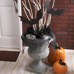 Ever wondered what to do with those cute, inexpensive urns from the crafts store? With a simple coat of spray paint they become spooky Halloween decorations. Stuff cotton batting and blocks of crafts foam inside. Stick white branches into the foam as desired. Cut-from-paper black bats, fabric leaves, black webbing, and a few creepy-crawly spider accents complete the look.