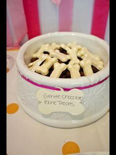 Puppy dog theme birthday party for girl. White chocolate bone treats on top of cocoa puffs in dog bowl from target