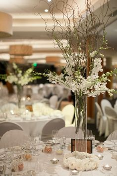 Rent tall cylinder vases and fill with willow branches and orchids for wedding centerpiece
