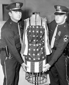 Patrolmen C.H. Vancil, left, and Wally M. Jernigan with a confiscated flag dress that landed Wade S. Wright, 23, and Roger W. Du Rand, 25, in hot water. The two were arrested on Sept. 17, 1968, on charges of desecrating an American flag. The dress was on display in their store, The Farthest Outpost, at 1106 Howard St. in Omaha. THE WORLD-HERALD