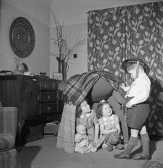 Doreen, Susie and Hugh Buckner play a game of 'Wardens' at their London home. Doreen, Susie and their dolls sit under an up-turned armchair covered in blankets, as 'Warden' Hugh checks to see that they are safely inside their make-believe air raid shelter.1943