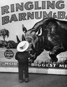 A young boy standing in front of a Ringling Bros. circus poster at Madison Square Garden. Photograph by Cornell Capa. New York City, 1953