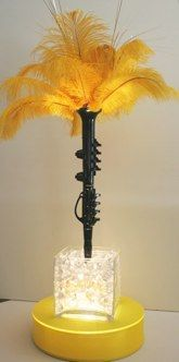 Love the use of the instruments- not sure you need the feathers...    Lighted Cube : Clarinet Centerpiece with Yellow Featherson Large Light Base with Yellow Gold spandex cover