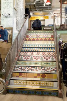 Rustic iron look stair rail and Moroccan tile riser on staircase. Eclectic and vintage