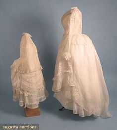 "MOTHER & DAUGHTER LINGERIE BUSTLE GOWNS, 1870s  Both white cotton gauze w/ vertical ruched bands alternating w/ Val lace, jackets fitted w/ long sleeves, skirts w/ overskirt: mother's has fitted open front jacket, 2 underskirts & 1 lace trimmed overskirt, B 36"", Jacket CB L 20"", W 24"", Skirt L 38""-47"", (overskirt w/ holes & tears, missing bottom flounces) good; child's jacket w/ CB buttons, skirt w/ attached overskirt,"