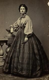 1861-1865 Garibaldi blouse, bow tie and plaid skirt.