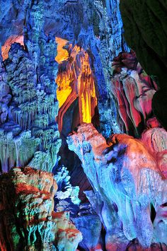 Lion Towards Rosy Dawn, Reed Flute Cave, Guilin, Guangxi, China., by Huang Xin.  Rosy Dawn in the Lion Hill in Reed Flute Cave, Guilin, Guangxi, China.  The Reed Flute Cave near Guilin is the most spectacular caves I have seen so far in China. It's a huge underground cave system with stunning rock formations, stalagmites and stalactites, illuminated with coloured lights. The cave can hold comfortably 1000 people.